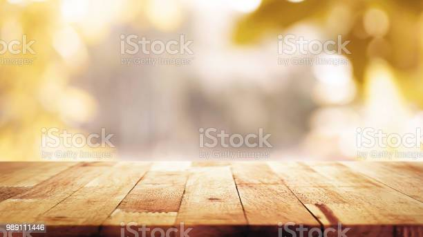 Photo of Wood table top on blur abstract natural foliage bokeh background, vintage tone