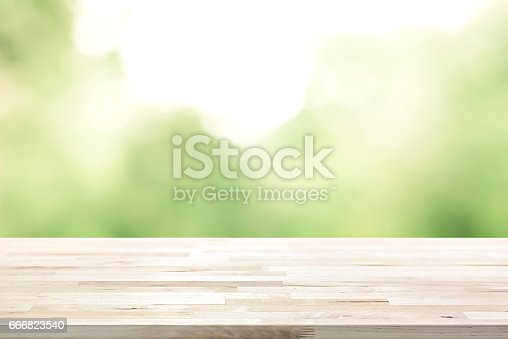 641254964 istock photo Wood table top on  blur abstract natural green background 666823540