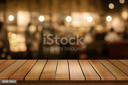 istock Wood table top on blur bokeh cafe background can be used for display or montage your products 655616642