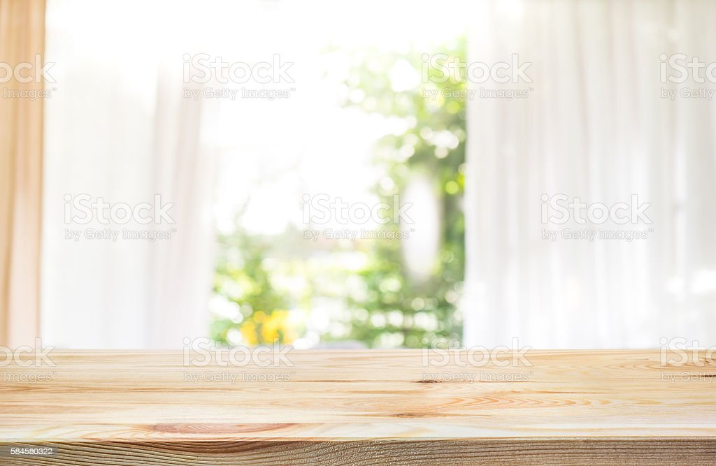 Wood table top on blur curtain window with green garden.