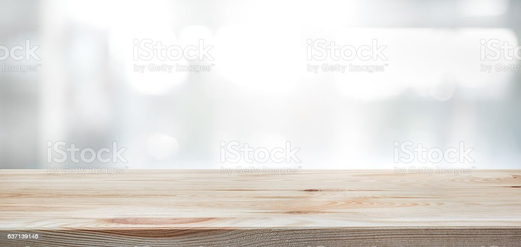 Wood table top on blur glass window wall background. stock photo