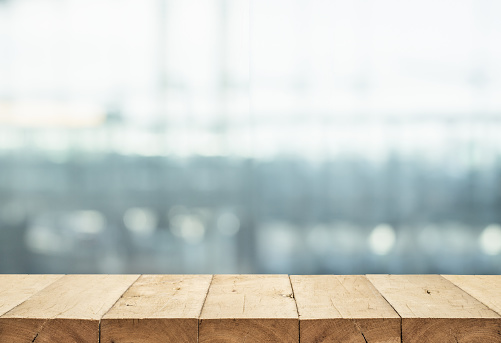 664975574 istock photo Wood table top on blur glass window wall building background. 914983226