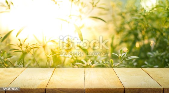 680878382istockphoto Wood table top on blur green abstract garden with sunlight. 680878382