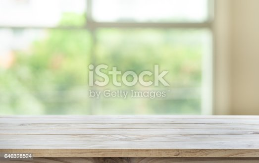680878382 istock photo Wood table top on blur green garden from window view. 646328524