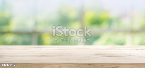 680878382istockphoto Wood table top on blur green garden from window view. 680874412