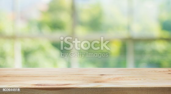 istock Wood table top on blur green garden from window view. 802644518