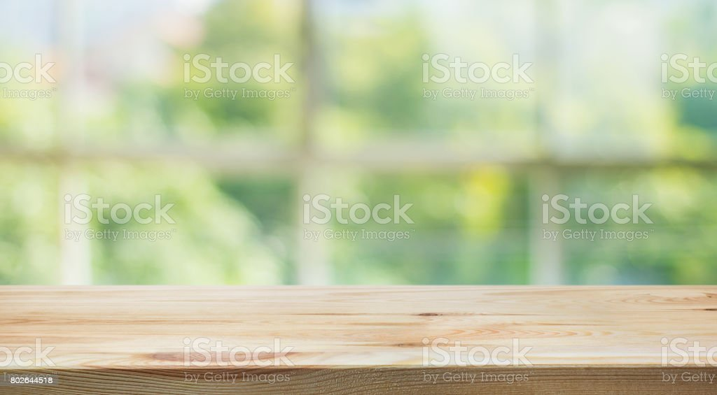 Wood table top on blur green garden from window view. stock photo