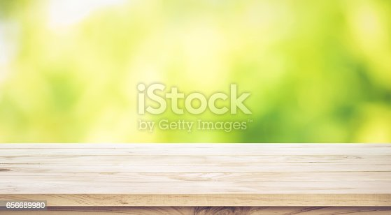 680878382istockphoto Wood table top on blur green garden in morning background. 656689980