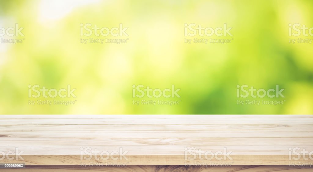 Wood table top on blur green garden in morning background. stock photo
