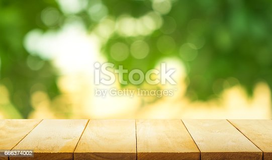 680878382istockphoto Wood table top on blur green garden in morning background. 666374002