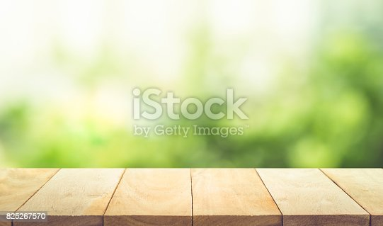 680878382istockphoto Wood table top on blur green garden in morning background. 825267570