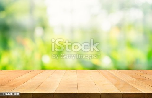 680878382istockphoto Wood table top on blur green garden in morning background. 840587488