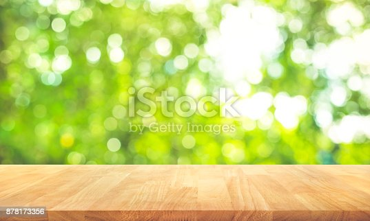 680878382istockphoto Wood table top on blur green garden in morning background. 878173356