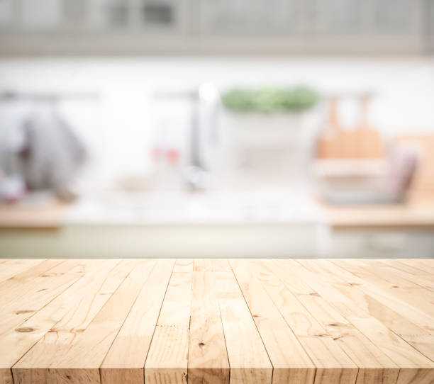Wood table top on blur kitchen counter (room)background.For montage product display or design key visual Wood table top on blur kitchen counter (room)background.For montage product display or design key visual layout. table stock pictures, royalty-free photos & images