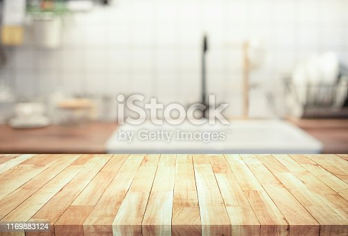 923629650 istock photo Wood table top on blur kitchen counter (room)background.For montage product display or design key visual 1169883124
