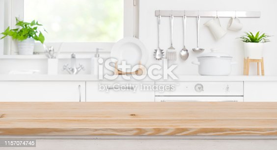 Wood table top on blur kitchen room and window background