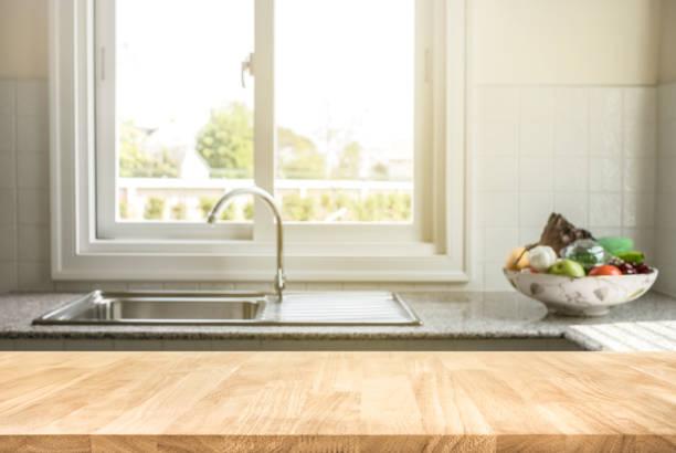 holz tischplatte auf küche zimmer hintergrund weichzeichnen - landküche stock-fotos und bilder