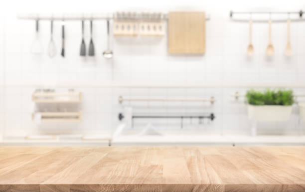 wood table top on blur kitchen room background - kitchen counter stock photos and pictures