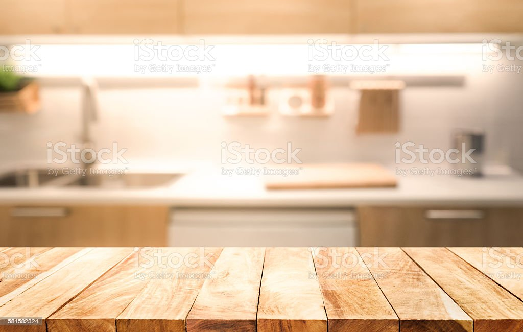 Wood table top on blur kitchen room interior background stock photo