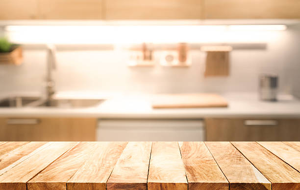 wood table top on blur kitchen room interior background - domestic kitchen stock photos and pictures
