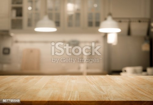 923629650 istock photo Wood table top on blur kitchen wall room background 867795548