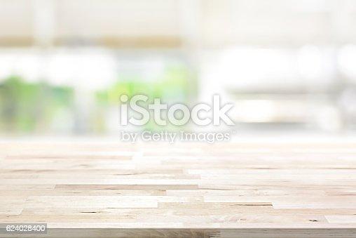 istock Wood table top on blur kitchen window background 624028400