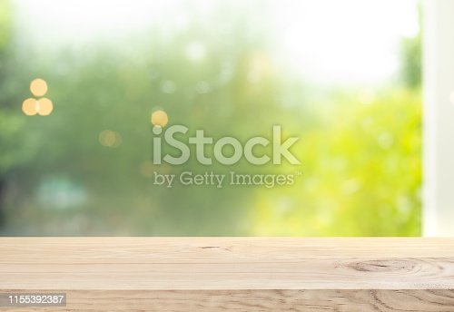 885452818istockphoto Wood table top (counter bar) on blur of window with beautiful garden in morning background 1155392387