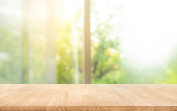 Wood table top (counter bar) on blur of window with beautiful garden in morning background stock photo