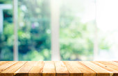 Wood table top on blur of window with garden flower