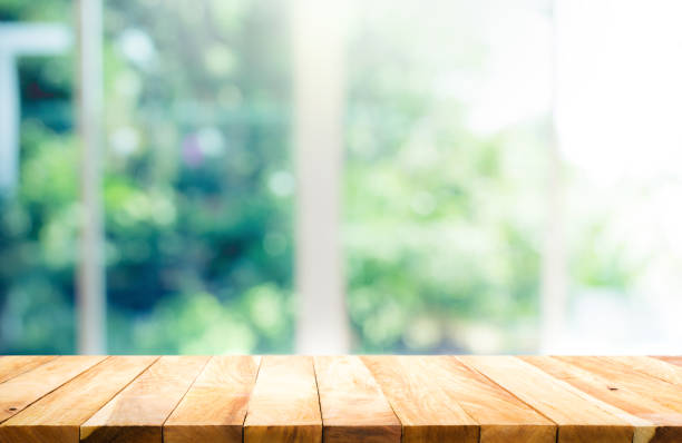 wood table top on blur of window with garden flower - home show stock photos and pictures