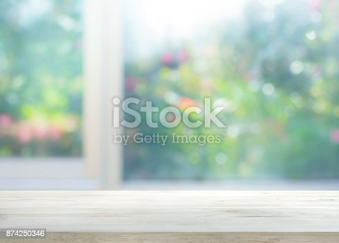 885452818istockphoto Wood table top on blur of window with garden flower 874250346