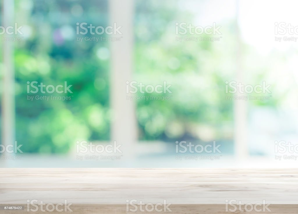 Wood table top on blur of window with garden flower stock photo