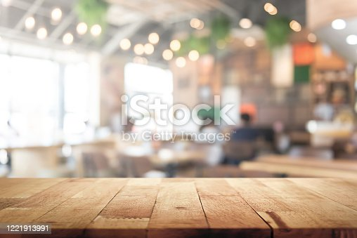 Wood table top on blur restaurant (cafe) interior background - can be used for display or montage your products (foods)