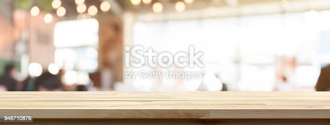 Wood table top on blur restaurant or cafe interior banner background - can be used for display or montage your products (food)