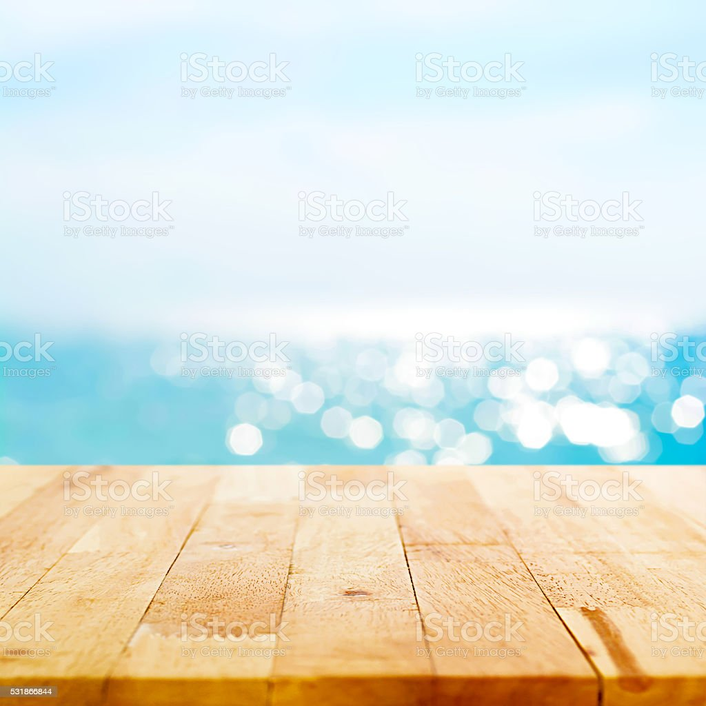 Wood table top on blur sparkling summer blue sea background stock photo