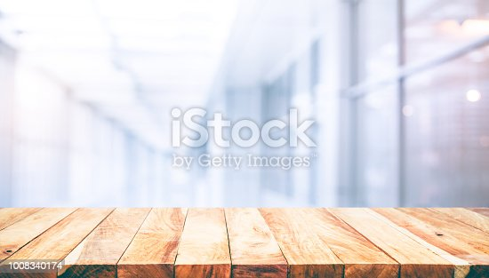 628471550 istock photo Wood table top on blur white glass wall background form office building.For montage product display and key visual layout 1008340174