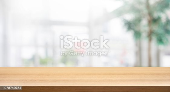 628471550 istock photo Wood table top on blur white glass wall background form office building.For montage product display and design key visual 1075749784