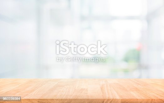 628471550 istock photo Wood table top on blur white glass wall background form office building 982239384
