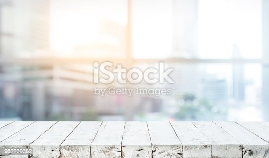 628471550 istock photo Wood table top on blur white glass window background form office building 982239362