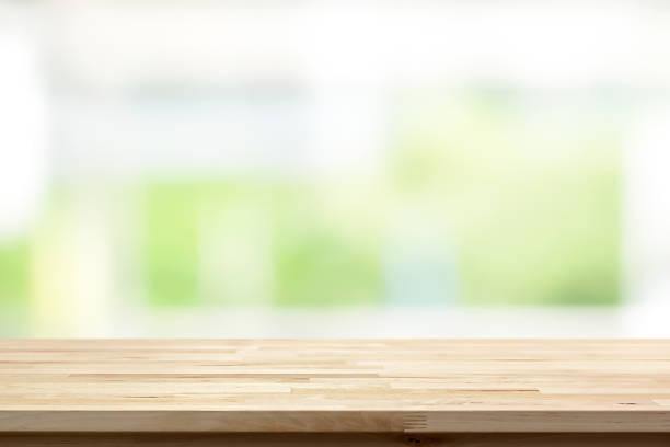 holz tischplatte auf weiße grüne küche fensterhintergrund weichzeichnen - landküche stock-fotos und bilder