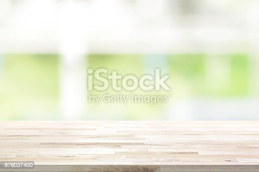istock Wood table top on blur white green kitchen window background 876037400
