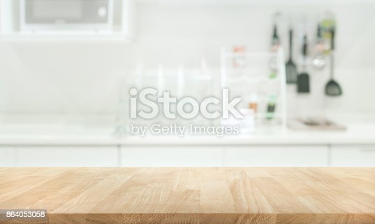 923629650 istock photo Wood table top on blur white kitchen wall room 864053058
