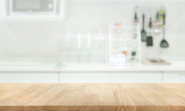 wood table top on blur white kitchen wall room - kitchen counter stock photos and pictures