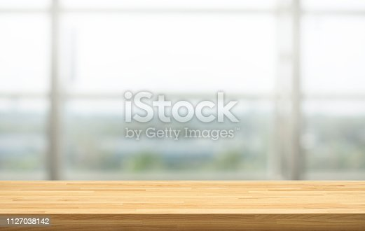 628471550 istock photo Wood table top on blur window glass, restaurant wall background.For montage product display or design key visual layout 1127038142