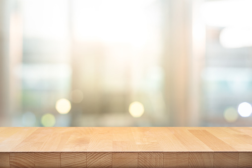 Wood table top on blur window glass,wall background