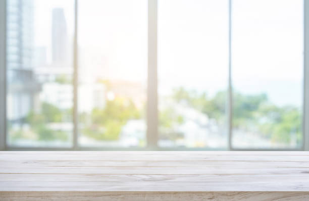 Wood table top on blur window glass,wall background with city view stock photo