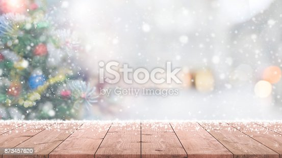 istock Wood table top on blur with bokeh christmas tree background with snowfall - can be used for display or montage your products. 873457620