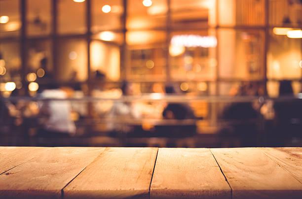 wood table top on blurred of cafe ( restaurant ) - goldene bar stock-fotos und bilder