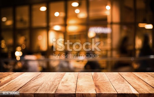 istock Wood table top on blurred of cafe ( restaurant ) with light gold in dark nigh background.For montage product display or key visual layout. 929760662