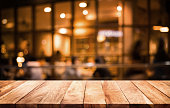 Wood table top on blurred of cafe ( restaurant ) with light gold in dark nigh background.For montage product display or key visual layout.